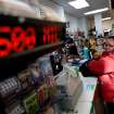 Pat Powell, 30, of Atlanta, buys a Powerball lottery ticket at a convenience store, Wednesday, Nov. 28, 2012, in Atlanta.