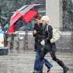 Two women share an umbrella to ward off snow as they walk the 16th Street Mall during the noon hour in Denver on Wednesday, April 17, 2013. As much as five inches of new snow is forecast for Denver. (AP Photo/Ed Andrieski)