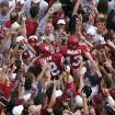Oklahoma fans surround former Sooner receivers Curtis Fagan (12) and Damian Mackey (13) after OU beat Nebraska 31-14 during the 2000 season. AP PHOTO