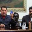 FILE - In this Dec. 8, 2012, file photo released by Miraflores Press Office, Venezuela's President Hugo Chavez, left, holds up a copy of the Venezuelan national constitution as his Vice President Nicolas Maduro looks on during a televised speech at Miraflores presidential palace in Caracas, Venezuela. Chavez has suffered
