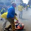 People react to a second explosion at the 2013 Boston Marathon in Boston, Monday, April 15, 2013. Two explosions shattered the euphoria of the Boston Marathon finish line on Monday, sending authorities out on the course to carry off the injured while the stragglers were rerouted away from the smoking site of the blasts. (AP Photo/The Boston Globe,  John Tlumacki) ORG XMIT: MABOD808