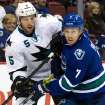 San Jose Sharks' Jason Demers, left, checks Vancouver Canucks' David Booth during first period NHL hockey action in Vancouver, British Columbia, on Thursday Nov. 14, 2013. (AP Photo/The Canadian Press, Darryl Dyck)