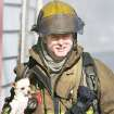 Oklahoma City firefighter C.J. Seitz carries a dog from a house fire in the 2400 block of NW 2 in Oklahoma City on Monday. Photo BY STEVE GOOCH, THE OKLAHOMAN