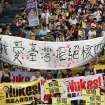 ADDS TRANSLATION OF THE BANNER IN CENTER - Protesters march during an anti-nuclear demonstration in Taipei, Taiwan, Saturday, March 9, 2013. Tens of thousands of Taiwanese have protested to demand that the government scrap a $10 billion nuclear power plant that is nearly complete and slated to begin operating in two years. The white banner reads: