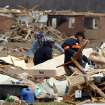 CORRECTS DAY OF STORM OUTBREAK TO FRIDAY - Dale Kirk, right, picks up a chair from the debris of the home of Brenda and Ted Tolbert of Holton, Ind. on Sunday, March 4, 2012 after tornadoes hit the area on Saturday. A string of violent storms scratched away small towns in Indiana and cut off rural communities in Kentucky as an early-season tornado outbreak struck on Friday, killing at least 37 people. (AP Photo/Ernest Coleman) ORG XMIT: INEC102