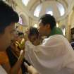CORRECTS MONTH - South Korean Catholic priest. Fr. Matthew Park, right, blesses devotees after the mass at the Our Lady of Remedies Parish Church in Manila, Philippines Sunday, Sept. 22, 2013. Catholics around the globe are expressing mixed but mostly positive reactions to Pope Francis' recent remarks that the church has become too focused on
