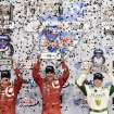 Tony Kanaan (center) holds the winners trophy along side teammate and second place finisher Scott Dixon (left), with third place finisher Ed Carpenter (right) following the IndyCar Series season final 500 mile auto race Saturday, Aug. 30, 2014, at Auto Club Speedway, in Fontana, Calif. (AP Photo/Will Lester)