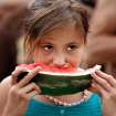 Lauren Atkins, 9, from Norman, eats free watermelon at the Norman Independence Day Celebration at Reaves Park in Norman, Okla., on Saturday, July 4, 2009.     Photo by Steve Sisney, The Oklahoman