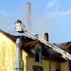 A firefighter extinguishes a fire in a house in Backnang,  Germany Sunday March 10, 2013. An early-morning fire on Sunday at the apartment building in southwestern Germany left seven people dead, six of them children, police said.  Authorities were alerted to the blaze in Backnang, a town near Stuttgart, at 4.30 a.m. Police said in a statement that they believe the fire broke out in a second-floor apartment, and said that their investigation is focusing on a heater in the apartment.  (AP Photo/dpa, Franziska Kraufmann)