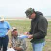 Biologist Don Wolfe, seated, takes measurements on a captured lesser prairie chicken as another biologist records data during a research field trip in Ellis County.  Photo Provided