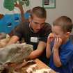 Liam Krivanek, a Mustang pre-kindergarten student, reacts to an animal skull held by Mustang student Harley Dodson. The hands-on exhibit was part of Mustang's first pre-kindergarten Science Discovery Day.  Community Photo By:  Shannon Rigsby, MPS  Submitted By:  Shannon, Mustang
