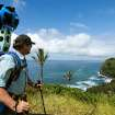 In this undated photo provided by Google, Rob Pacheco, president of Hawaii Forest & Trail, takes in the view at Pololu Valley's Awini Trail near Kapaau, Hawaii, while wearing the Street View Trekker. Hawaii's volcanoes, rainforests and beaches will soon be visible on Google Street View. The Mountain View, Calif., company said Thursday June 27, 2013  it was lending its backpack cameras to a Hawaii trail guide company to capture panoramic images of Big Island hiking trails. (AP Photo/Google)