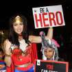 Miss Universe 2005 Natalie Glebova of Canada, wearing Wonder Woman costume poses with Thai children during Convention on International Trade in Endangered Species, or CITES, in Bangkok, Thailand Sunday, March 3, 2013. How to slow the slaughter and curb the trade in