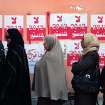 Egyptian women line up outside a polling station next to stickers on a wall with Arabic writing that reads