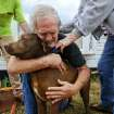 Greg Cook hugs his dog Coco after finding her inside his destroyed home  in the East Limestone, Ala. on Friday, March 2, 2012.  A reported tornado destroyed several houses in northern Alabama as storms threatened more twisters across the region Friday  (AP Photo/The Decatur Daily, Gary Cosby Jr.) ORG XMIT: ALDEC102