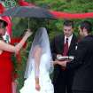 Bridesmaid Heather Mendez tries tries to keep rain off a bride Sunday at the Myriad Gardens in Oklahoma City. Rocky Addington married Crystal Mendez as Lake Carpenter officiated the cerimony. A sudden shower began during the wedding, on a rainy Memorial Day weekend.  Community Photo By:  Isaac Goodman  Submitted By:  Isaac, Piedmont