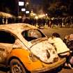 In this Monday, Jan. 28, 2013 photo, an Egyptian protester take cover beside a vehicle damaged during clashes between protesters and Egyptian security forces in Downtown Cairo, Egypt. On Tuesday, Jan. 29, 2013, Egypt's army chief warns of