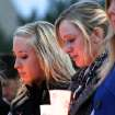 In this Nov. 7, 2012 photo, Northern Illinois University students Mary Jane Meisenheimer, left, and Lindy Luchowski, both friends of David Bogenberger, participate in a candlelight vigil for Bogenberger outside the Holmes Student Center in DeKalb, Ill. Nearly two dozen Pi Kappa Alpha members at Northern Illinois University have been charged with hazing-related counts after Bogenberger was found dead at their fraternity house following a night of drinking. (AP Photo/Daily Chronicle, Kyle Bursaw) CHICAGO LOCALS OUT; ROCKFORD REGISTER STAR OUT; MANDATORY CREDIT