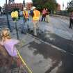 In this photo taken with a fisheye lens, a young fan, foreground, looks across police tape at two workers from the Denver Water Department toil at the site of a water main break in front of Coors Field which forced the cancellation of a baseball game between the Cincinnati Reds and the Colorado Rockies in Denver on Saturday, Aug. 16, 2014. The game will be made up as part of a split doubleheader on Sunday. (AP Photo/David Zalubowski)