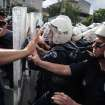 Riot police try to stop protesters who were attacking the offices of Prime Minister Recep Tayyip Erdogan's Justice and Development Party, in Soma, Turkey, during his visit to the coal mine in Soma Wednesday, May 14, 2014.  A violent protest erupted Wednesday in the Turkish city of Soma, where at least 238 coal miners have died after a mine explosion as many in the crowd expressed anger at Prime Minister Recep Tayyip Erdogan's government, rocks were thrown and some people were shouting that Erdogan was a