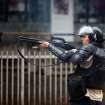 A Bolivarian National Police officer fires rubber bullets at demonstrators after clashes broke out at an at anti-government protest in Caracas, Venezuela, Thursday, May 8, 2014. Demonstrators took to the streets after a pre-dawn raid by security forces that broke up four camps maintained by student protesters and arrested more than 200 people. The tent cities were installed more than a month ago in front of the offices of the United Nations and in better-off neighborhoods in the capital to protest against President Nicolas Maduro's socialist government. (AP Photo/Alejandro Cegarra)