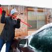 Snowfall came to an end  Friday night and many Oklahomans spent time Saturday, Jan. 30, 2010, clearing snow and ice from their vehicles, driveways and sidewalks. A woman who gave her name as Florence uses the handle of a broom to break thick ice on her car's hood and windshield in the parking lot of her Del City apartment.  Photo by Jim Beckel, The Oklahoman