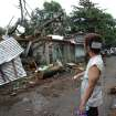 Injured resident Arnel Castillo looks at the damage to his home caused by a fallen tree from Typhoon Koppu in suburban Quezon city, north of Manila, Philippines on Monday, Oct. 19, 2015. Army, police and civilian volunteers scrambled Monday to rescue hundreds of villagers trapped in flooded homes and on rooftops in the northern Philippine province battered by slow-moving Typhoon Koppu. (AP Photo/Aaron Favila)