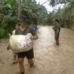 In this photo taken Tuesday, Dec. 4, 2012 and released by the Philippine Army, a soldier of the 71st Infantry Battalion, 1001st Infantry Brigade of the Philippine Army assists a local resident to carry a sack along a flooded area in Compostela Valley, southern Philippines. The death toll from Typhoon Bhopa climbed to more than 100 people Wednesday, Dec. 5, while scores of others remain missing in the worst-hit areas of the southern Philippines. (AP Photo/The Philippine Army) NO SALES