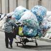 A collector of recyclable bottles and cans that can be redeemed for a cash deposit, takes advantage of the recycling that has piled up on William Street, one block from the New York Stock Exchange, Thursday, Nov. 8, 2012 in New York. Recycling pickup has been suspended in the wake of Superstorm Sandy. (AP Photo/Henny Ray Abrams) ORG XMIT: NYHA11