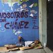 Homeless Efrain Juanipas, 37, rests on a makeshift bed made from a a cardboard box next to graffiti that reads in English: