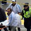 Medical workers aid injured people at the finish line of the 2013 Boston Marathon following an explosion in Boston, Monday, April 15, 2013. Two explosions shattered the euphoria of the Boston Marathon finish line on Monday, sending authorities out on the course to carry off the injured while the stragglers were rerouted away from the smoking site of the blasts. (AP Photo/The Boston Globe, David L Ryan)   ORG XMIT: MABOD802