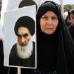 An Iraqi woman living in Iran holds a poster of the Grand Ayatollah Ali al-Sistani, Iraq's top Shiite cleric, in a demonstration against Sunni militants of the al-Qaida-inspired Islamic State of Iraq and the Levant, or ISIL, and to support Ayatollah al-Sistani, in Tehran, Iran, Friday, June 20, 2014. (AP Photo/Ebrahim Noroozi)