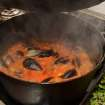 Steam rises from a pot of Italian Fish Soup as it cooks on a stove. (Johnny Crawford/Atlanta Journal-Constitution/MCT)