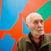 In this Sept. 24, 2013 photo, artist Robert Indiana, known world over for his LOVE image, is interviewed in front of that painting at New York's Whitney Museum of American Art. Surrounded by 95 works he created over the past five decades, Indiana, who turned 85 this month, calls the retrospective