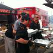 From left, OSU basketball coach Travis Ford, Tommy Wade, OSU's director of player development, and Lt. Leon Jones of the OSU Police Department help cook hamburgers in the parking lot of the Home Depot in Moore on Friday. PHOTO BY BERRY TRAMEL, THE OKLAHOMAN KOD