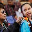 Gabrielle Gallegos, 8, gets help with her costume from her grandmother,  June Carpitcher of Oklahoma City. Gabrielle is a member of the   Seminole Nation, but for the pow-wow, she dressed in Ponca attire to perform in the southern cloth dances.  At least 500 people representing several dozen Native American Nations within the state attended  a New Year's pow-wow in the Centennial Building at State Fair Park Saturday , January 7, 2012,   The celebration started around shortly after noon and continued into the night.   Several hundred took part in the various dancers and the dancers wore tribal regalia.  Photo by Jim Beckel, The Oklahoman