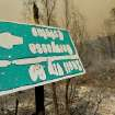 A sign, melted in the intense heat of the Butts Fire, gives arrows for Snell Valley Road and Berryessa Estates, Wednesday, July 2, 2014, near Middletown Calif. By early evening, the Butts Fire in remote Pope Valley grew to 3,800 acres from 3,200 acres, said Daniel Berlant, a spokesman for the California Department of Forestry and Fire Protection. The blaze is not threatening any major vineyards, Berlant and a spokeswoman for a vintners association said.  (AP Photo/Santa Rosa Press Democrat, Kent Porter)
