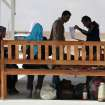 A newly-arrived Syrian refugee family waits under a shaded area upon their arrival to the new Jordanian-Emirati refugee camp, Mrajeeb al-Fhood, in Zarqa, Jordan, Wednesday, April 10, 2013. A second camp for Syrian refugees has opened in Jordan as more Syrians flee the civil war at home. The Jordanian-Emirati camp is the first funded by the United Arab Emirates and run by its Red Crescent Society in Jordan to assist families, single women, the disabled, and elderly.(AP photo/Mohammad Hannon)