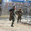 Soldiers run during clashes with the relatives of inmates after a deadly prison fire in Comayagua, Honduras, 90 miles (140 kilometers) north of the capital, Tegucigalpa, Honduras, early Wednesday Feb. 15, 2012. At least 300 inmates were killed and 21 are injured, according to authorities. (AP Photo/Fernando Antonio)