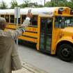 Ronald E. McNair Discovery Learning Academy assistant principal Johnny Potter waves to a bus Wednesday, Aug. 21, 2013, a day after an armed suspect cause an ordeal at their school in Decatur, Ga. The learning academy held classes at McNair High School on Wednesday after a gunman on Tuesday held one or two staff members captive and fired into the floor of the school office. As officers swarmed the campus outside, he shot at them at least a half a dozen times with an assault rifle from inside the school and they returned fire, police said. (AP Photo/Atlanta Journal-Constitution, Jason Getz)