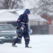 COLD WEATHER / WINTER STORM / SNOW / POSTAL CARRIER / MAILMAN / POSTMAN: Mail carrier David Alexander lowers his head and walks through snow delivering mail in a Midwest City neighborhood near SE 15 and Lockheed.  Alexander, who has worked for the post office for 26 years, said the most difficult part of delivering the mail in this weather is walking through the snow. He said the sub-freezing temperatures don't bother him too much because he dresses for the cold. He wears five layers of clothing above the waist and three layers of clothing below the waist. He wears thermal undershirts and pants. On his feet, he wears boots.  He wears gloves and a mask around his face. A second winter storm in a week dumped about 6 inches of snow in the Oklahoma City area Tuesday morning, Feb. 9, 2011.   Photo by Jim Beckel, The Oklahoman ORG XMIT: KOD