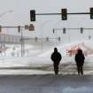 Two people walk north on Shields Boulevard into the downtown area as the sun emerges briefly from heavy clouds. A  severe winter storm created whiteout conditions and caused snow drifts that made problems for the few motorists who ventured out Tuesday afternoon, Feb. 1, 2011.   Photo by Jim Beckel, The Oklahoman