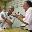 John Sacco Sr. hands his 6-month-old grandson, Jack Russo, to Pete Canu, a customer in Sacco's Elizabeth, N.J., butcher shop, Thursday, June 20, 2013. Canu says he liked the realism and human flaws of actor James Gandolfini's Tony Soprano character, but Sacco said,