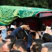 People carry the coffin of a mine accident victim for burial in Soma, Turkey, Wednesday, May 14, 2014.   Nearly 450 miners were rescued, the mining company said, but the fate of an unknown number of others remained unclear as bodies are still being brought to the surface and burials are underway after one of the world's deadliest mining disasters.(AP Photo/Emre Tazegul)