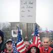 People hold United States flags during a pro-gun rally at the Washington state Capital in Olympia, Washington on Saturday, Jan. 19, 2013. (AP Photo/The News Tribune, Lui Kit Wong)
