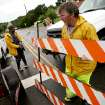 City employee Gil Barnes, puts up a roadblock at Hefner road and Macarthur as water spills over the dam south of Hefner between Macarthur and Rockwell in Oklahoma City on Monday, June 14, 2010. Photo by John Clanton, The Oklahoman