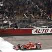 Tony Kanaan takes the checkered flag to win the IndyCar Series season final 500 mile auto race Saturday, Aug. 30, 2014, at Auto Club Speedway, in Fontana, Calif. (AP Photo/Will Lester)