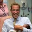 FILE - In this Wednesday Sept. 20, 2006 file photo Britain's Prince William holds baby Sina Nuru in the new Winnicott Baby Unit at the St Mary's Hospital, in London. It was announced  on Monday, July 22, 2013, in London that Kate, Duchess of Cambridge and her husband Prince William, the Duke of Cambridge, gave birth to a boy weighting 8lbs  6 oz.  (AP Photo/Tom Hevezi, File)