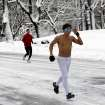 A shirtless jogger runs through New York's Central Park Saturday, Feb. 9, 2013. In New York City, the snow total in Central Park was 11.4 inches by 8 a.m. (AP Photo/Richard Drew)