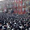 In this March 3, 2013, photo provided by VosIzNeias.com, Orthodox Jewish mourners gather outside the Congregation Yetev Lev D'Satmar synagogue in Brooklyn's Williamsburg neighborhood for the funeral of two expectant parents who were killed in a car accident early Sunday, in New York. The baby of Nachman and Raizy Glauber, a boy, was delivered prematurely by cesarean section and survived until the next morning, but died around 5:30 a.m. on Monday,March 4. Police were searching for the driver of a BMW and a passenger who fled on foot after slamming into the livery cab that was transporting the 21-year-old couple to a hospital. (AP Photo/VosIzNeias.com, Eli Wohl)